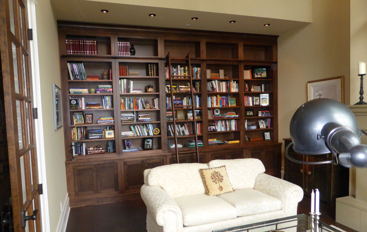 custom home library with rolling library ladder
